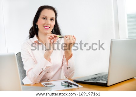 young  businesswoman filing her nails while sitting at her desk in the office - stock photo