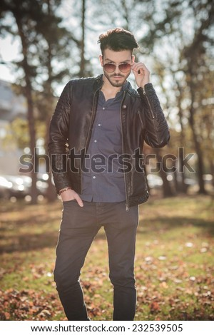 Young casual man looking at the camera over his sunglasses while holding one hand in his pocket, Outdoor picture. - stock photo
