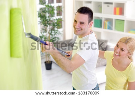 Young cheerful couple painting their home, concept renovation - stock photo