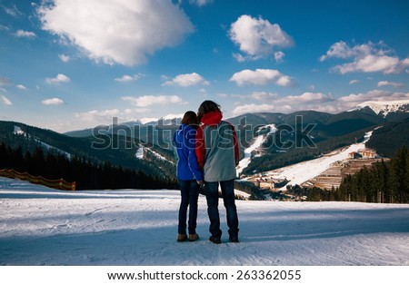 young couple relax at top of mountain at beautiful sunny winter day - stock photo