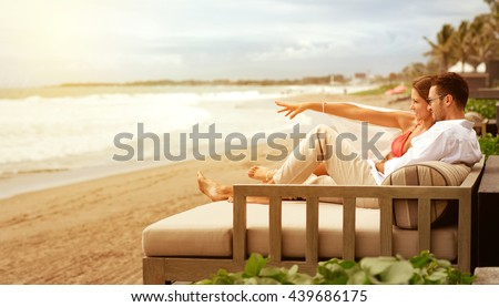 Young couple relaxing on sunbed n beautiful beach