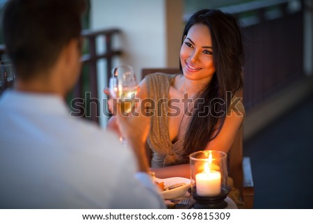 young couple with a romantic dinner with candles on tropical balcony  - stock photo