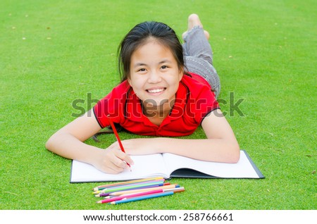 young cute  girl  asian drawing in the park on the grass - stock photo