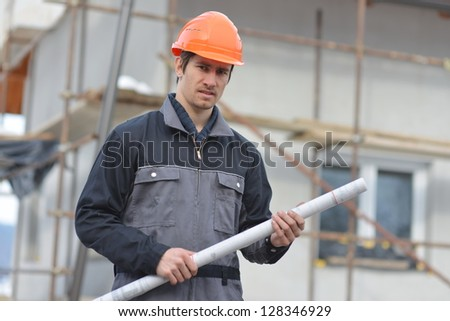 Young engineer holding blueprint on the construction site