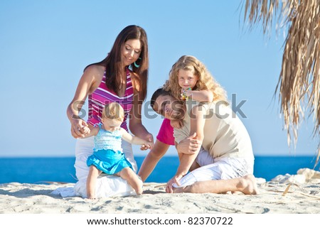 young family having fun on the beach