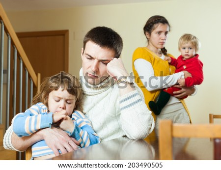 Young family of four having quarrel at home - stock photo
