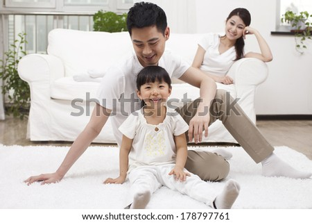 Young family sitting in couch - stock photo