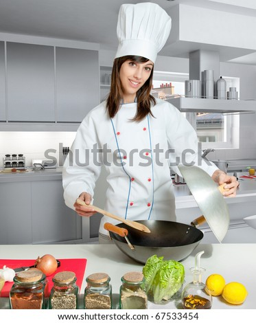 Young female chef with a wok in a kitchen interior - stock photo