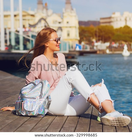 Young fresh  pretty woman sitting on  wooden pier  near sea and looking at  the city. Attractive hipster girl with back pack enjoying  her holidays. .Active lifestyle concept.  - stock photo