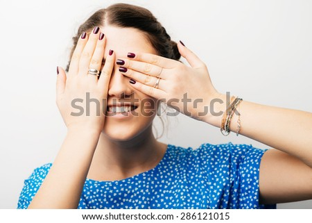 young girl closes eyes with her hands - stock photo