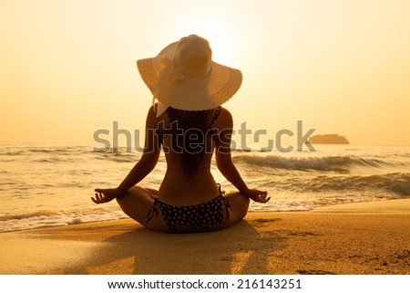 Young girl in a straw hat on a tropical beach at sunset. Summer vacation concept. - stock photo