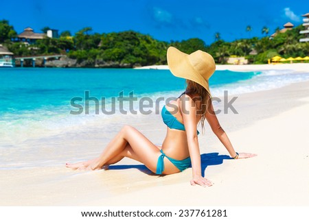 Young girl in a straw hat on a tropical beach. Summer vacation concept.