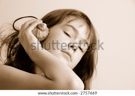Young girl listening to the seashell