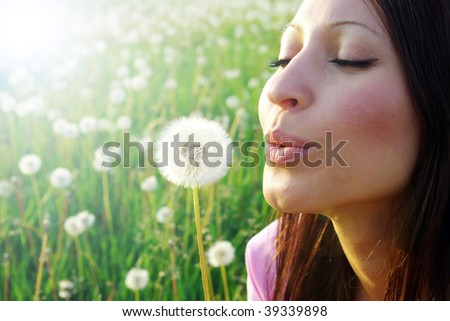 young girl playing with dandelion