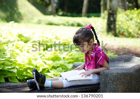 Young girl reading a book in the park - stock photo