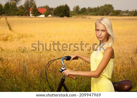 Young girl with a bike on the wheat field background. - stock photo