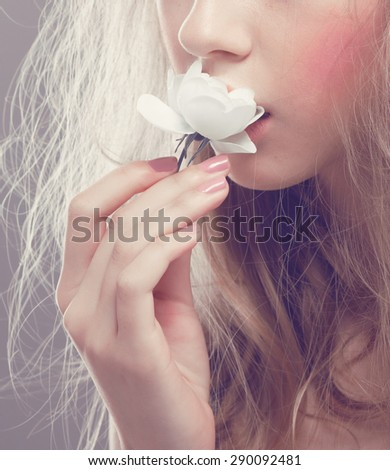 young girl  with a white flower, isolated grey background - stock photo