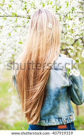 young girl with beautiful long hair in the spring garden - stock photo