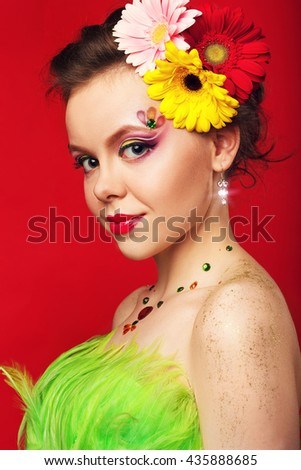 young girl with fantasy makeup on red background.