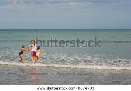 3 young girls in the surf