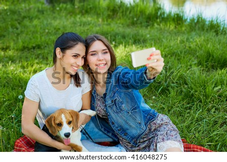 Young girls taking photo of herself and her dog outdoor in nature. - stock photo