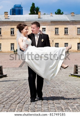 Young groom holding bride on hands and walking - stock photo