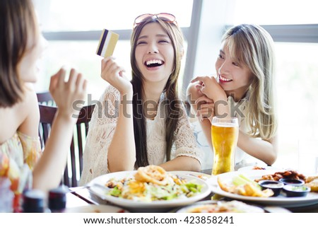 young group showing credit card and chatting in restaurant