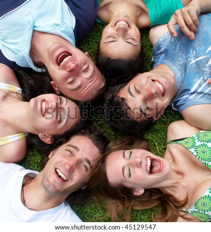 Young guys and girls lying on grass looking up - stock photo