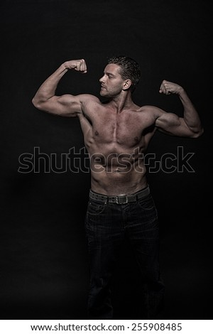 Young handsome athletic man with naked torso on dark background with copyspace - stock photo