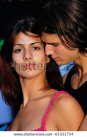 young handsome couple in front of graffiti wall - stock photo