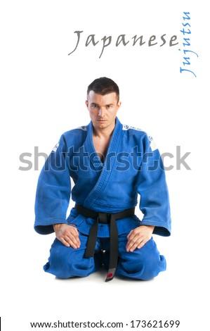 Young handsome man practicing jiu-jitsu (Hakki Heysen Ryu school) isolated on white background - stock photo