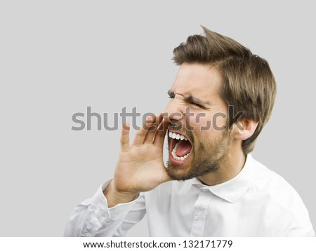 young handsome man shouting isolated over gray background