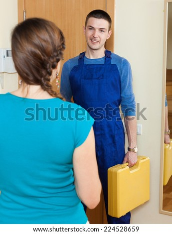 Young happy service worker came to help the young the woman  - stock photo