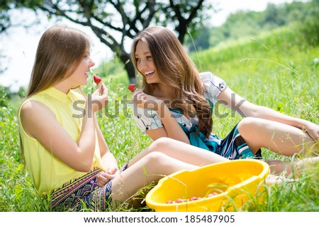 2 young happy smiling pretty women two teen girl friends having fun eating strawberry from huge bowl on summer day outdoors background - stock photo