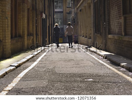 2 young lads walking down a long dark back alley - stock photo