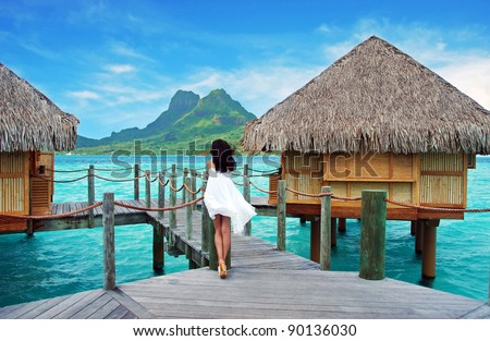 Young lady stand alone , look towards to the Otemanu mountain at Bora Bora island , French Polynesia , Pacific ocean . - stock photo