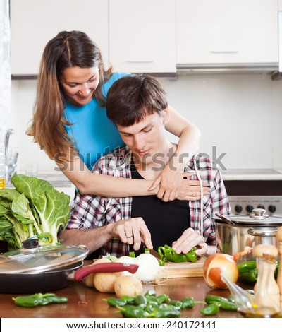 young loving couple cooking with  fresh vegetables and greens in home kitchen