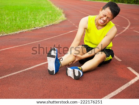 young male runner suffering from leg cramp on the track in the stadium - stock photo