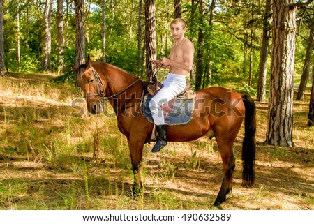 young man in the forest on horseback
