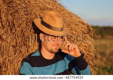 young man on a haystack in a straw hat