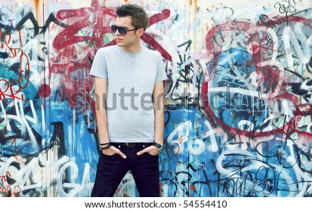 young man posing in front of a colorful graffiti wall