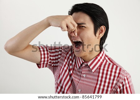 young man pressing his nose - stock photo