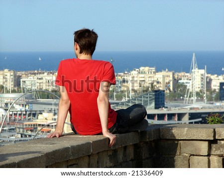 young man sitting on a parapet and looking to barcelona