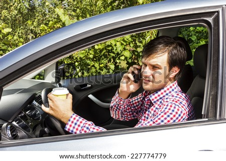 Young man speaking on phone and drinking coffee while driving his car  - stock photo