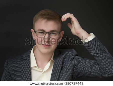 Young man wearing glasses and a business suit. Black background. - stock photo