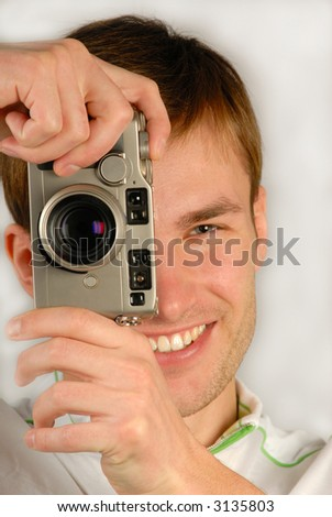 young man with  camera in hands is going to photograph, close up - stock photo