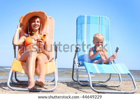 young mother with little daughter on the beach - stock photo