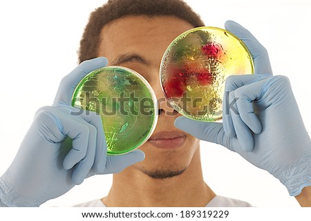 Young mulatto chemist  with petri boxes, over white background - stock photo