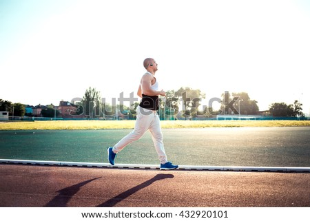 Young muscular man running in the stadium on the open air at sunset