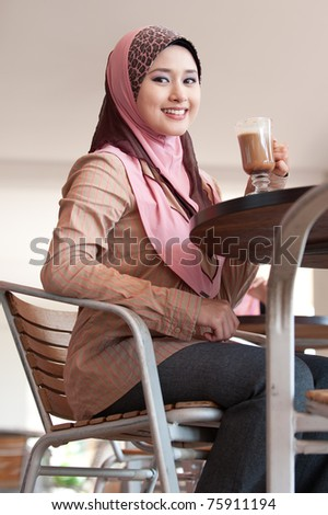 young muslim woman in head scarf drink in cafe